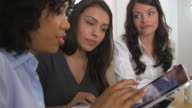 Three business women using tablet pc together