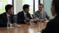 MS Three businessmen meeting with businesswoman in conference room / Beijing, China