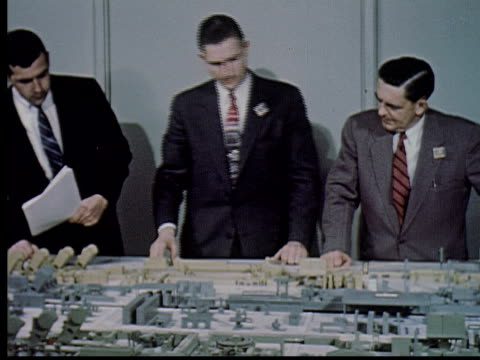 MS, COMPOSITE, CU, Three businessmen standing at table pointing at architectural model of factory complex, USA