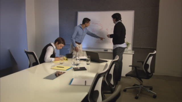 Three businesspeople discussing drawings on white board in board room, one taking notes / New York City, New York, USA