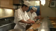 Three chefs preparel sushi ovals behind the counter of a sushi shop.