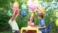 Three child at a birthday party in the garden