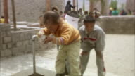 MS, SELECTIVE FOCUS, Three children (8-9, 10-11) gathering water from outdoor water tap, Ladakh, Jammu and Kashmir, India