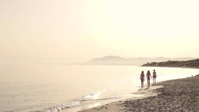 Three children running and walking to camera on beach.