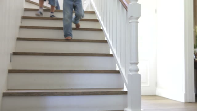 Three Children Running Down Stairs At Home