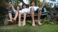 MS Three children sitting on swing / Fujikawaguchiko, Yamanashi, Japan