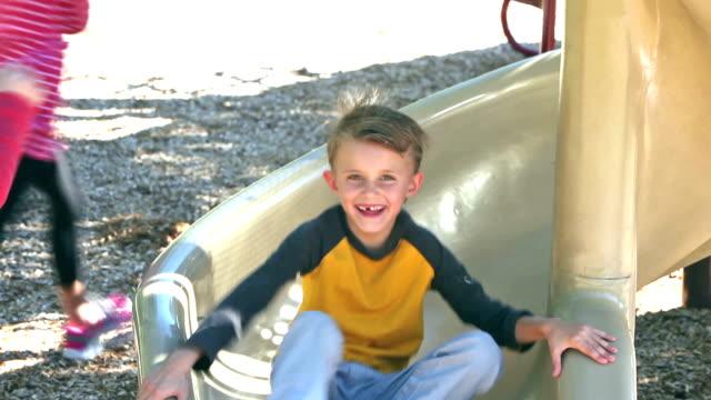 Three children sliding down slide on playground