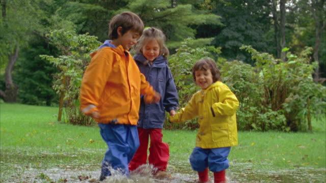 MS, Three children (3-7) wearing raincoats splashing puddle, Yarmouth, Maine, USA