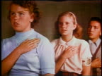 1953 three children with hands on chests saying Pledge of Allegiance then sitting down