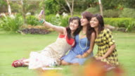 Three college students taking photographs with a mobile phone