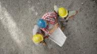LD drei Bauarbeiter, die Prüfung der Pläne auf der Baustelle