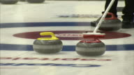 Three curling stones near house at end of ice curling sheet one yellow stone two red stones unidentifiable player putting curling broom into frame on...