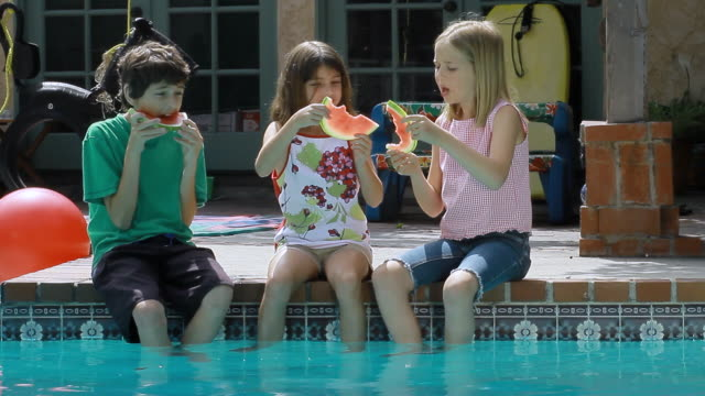 MS Three cute children eating watermelon at swimming pool / Los Angeles, California, United state