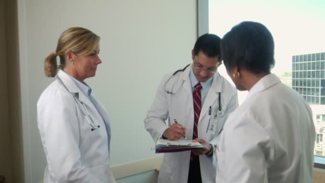 MS Three doctors signing patient's chart and shaking hands, Seattle, Washington, USA