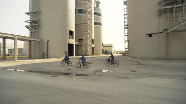 WS PAN ZI Three employees riding bicycles on grounds of Huaneng Yuhuan power plant, Yuhuan County, Zhejiang, China