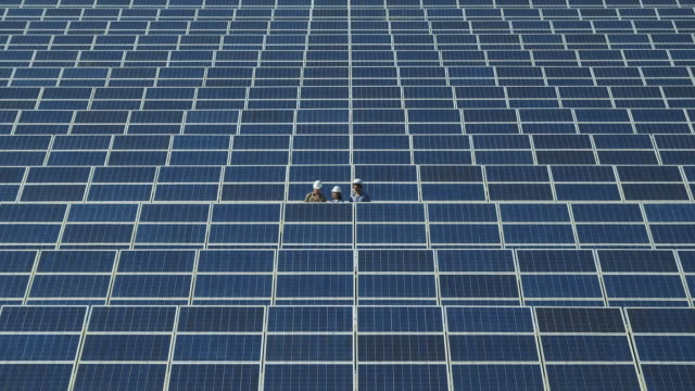 WS Three engineers standing in photovoltaic (solar) plant / Malaga, Spain
