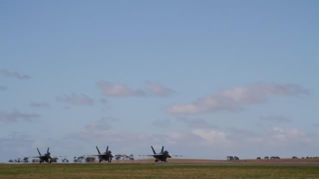 Three F/A-18F Super Hornet fighter jets taxi on runway, Australia