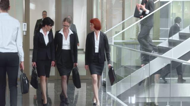 DS Three female businesswomen talking and walking down hallway