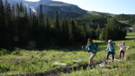 Three female friends hike together thru mountain meadow