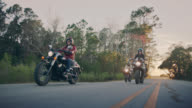 SLO MO. Three female friends ride motorcycles down coastal highway at sunset.