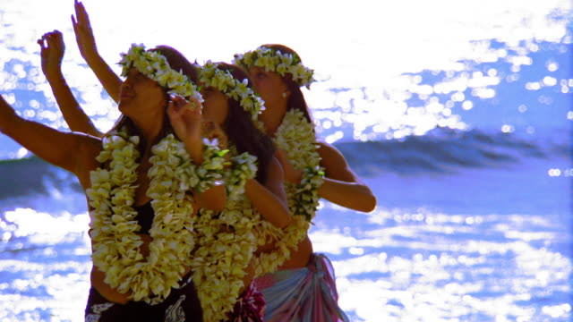 MS three female hula dancers standing together doing arm movements in unison / ocean in background / Hawaii