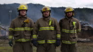 Three firemen stand in front of the smoldering ruins of a house