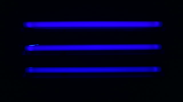 Three fluorescent blue stip lights are switched on in a dark room.
