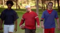 Three football players walking towards camera