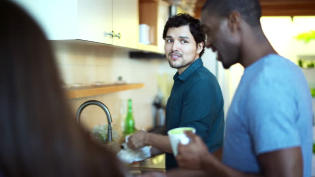 Three friends, black and Hispanic males and white female, meeting in the kitchen
