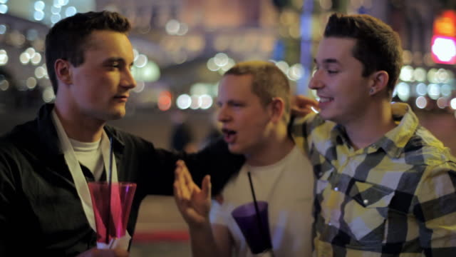 Three friends stand on a sidewalk in Las Vegas holding large alcoholic drinks.