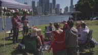 Three generation family sitting talking and laughing with picnic rugs on the ground sun shade and Brisbane River and skyline in the background /...
