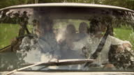 MS, Three generation family with boy (6-7) and girl (10-11) traveling in car seen through windshield, Tamborine Mountain, Brisbane, Queensland, Australia