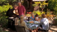 MS, Three generation family with girl (4-5) having barbecue in garden, Cambria, California, USA