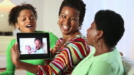MS Three Generations of Women Video Chatting with Young Girl and Baby on Tablet Computer / Richmond, Virginia, USA