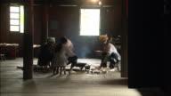 Three generations of Zhuang women cooking at open fire in home, Ping'an village, Guilin, Guangxi Zhuang