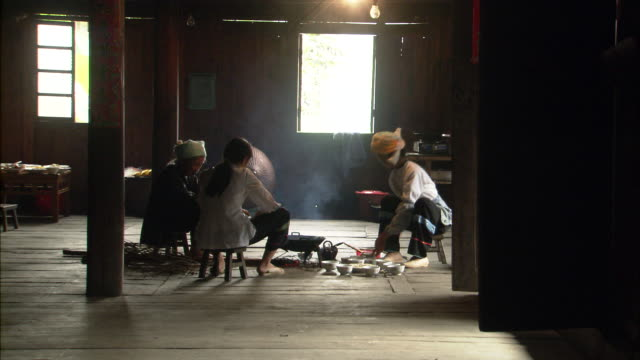 Three generations of Zhuang women cooking at open fire in home, Ping'an village, Guilin, Guangxi Zhuang