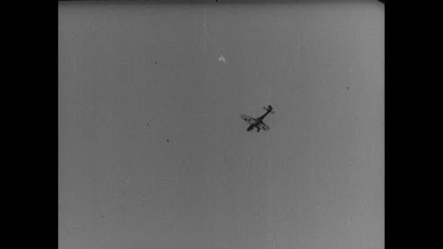 Three German bombers diving / shot inside cockpit of pilot releasing bomb / aerial shot of bombs exploding on ground / two German bombers diving and...