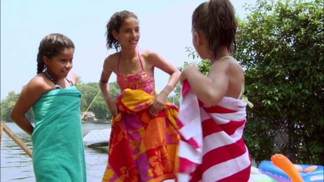 Three girls dressed in bathing suits standing near lake and drying off with towels / New Jersey