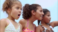 Three girls dressed in bathing suits with excited expressions / New Jersey