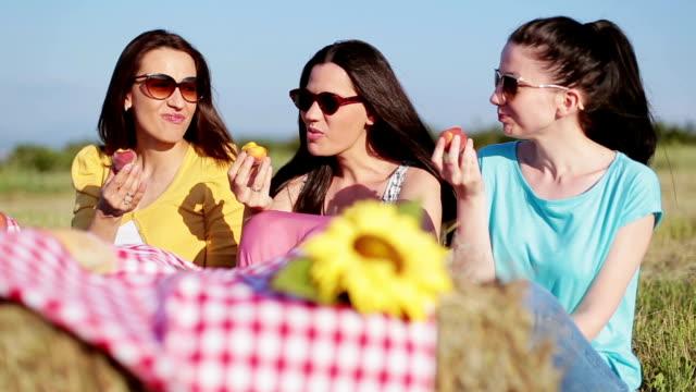 Three girls eating peaches on picnic