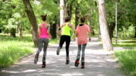 Three girls jumping with kangoo shoes in the park