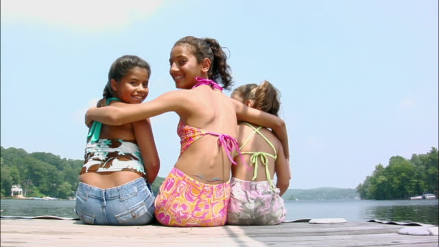 Three girls sitting at end of dock on lake looking over shoulder and smiling at camera / girl in middle with arms around other girls / New Jersey