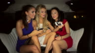 WS Three girls using smartphones in Limousine