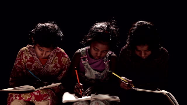 Three girls writing on a book