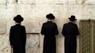 Three Hasidic men pray at the Wailing Wall