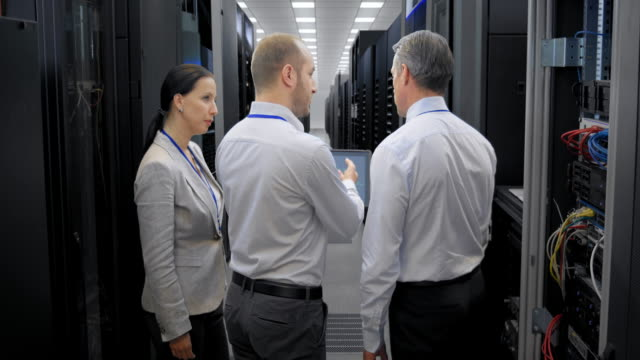 LD Three IT engineers talking in the server room