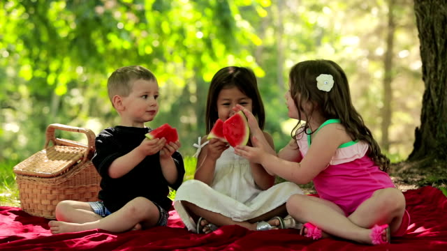 Three kids have fun eating fruit together