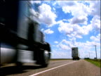 Three lorries speed along long straight stretch of highway under sunny and cloudy sky USA