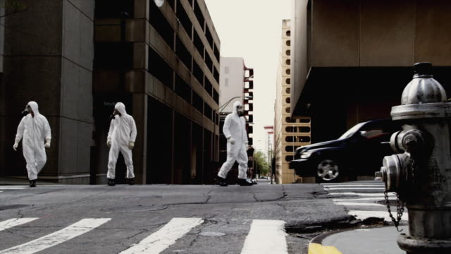 WS Three men in HAZMAT suits walking along street, Atlanta, Georgia, USA