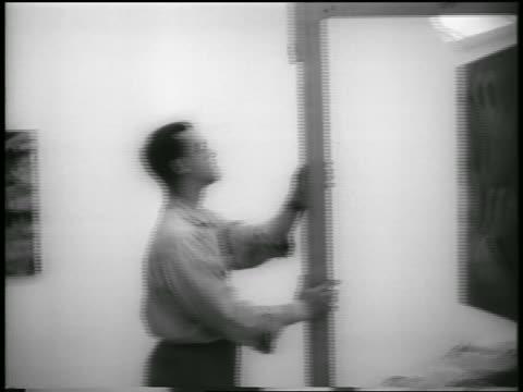 PAN three men installing painting in Guggenheim Museum / NYC / newsreel